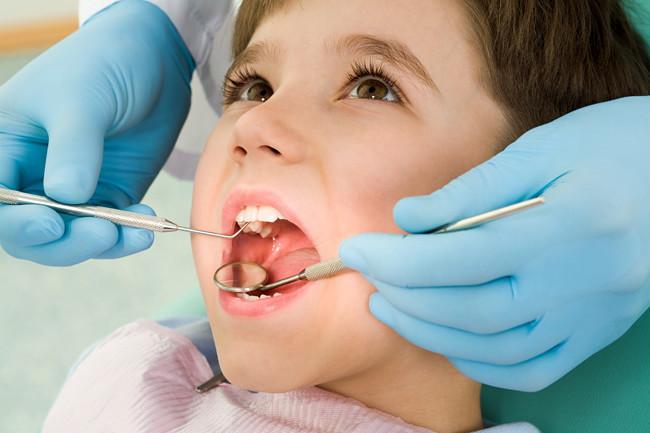 tandläkare undersöker pojke